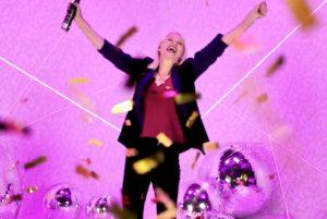 Woman standing in gold confetti holding confetti cannon
